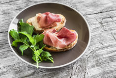 Toast with ham and fresh arugula on a brown plate Royalty Free Stock Images