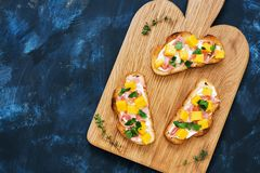 Toast with ham jamon avocado and cream cheese on a cutting board, blue fashioned rustic background, top view. Stock Image