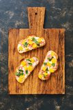 Toast with ham and mango on wooden Board, dark background, top view. Royalty Free Stock Image