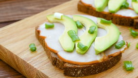 Toast with ham and slices of avocado stock video