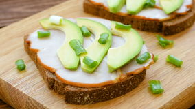 Toast with ham, slices of avocado and green onion stock footage