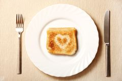 Toast and heart on a plate Stock Photos