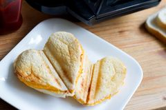 Toast heart shape with toaster sandwich maker love valentines breakfast concept. Closeup stock image