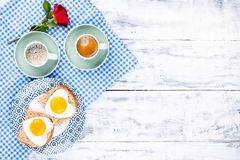 Toast with a heart-shaped egg on a plate and 2 cups of coffee. Romantic breakfast for two. Red rose and morning surprise for royalty free stock photos