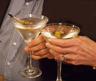 A toast heres to you. A man and a woman at a festive occasion with a toast over two martinis.  each martini has three olives on a toothpick.  The woman is graced Royalty Free Stock Images