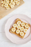 Toast with homemade peanut butter and banana on a white table. Top view. Selective focus Royalty Free Stock Images