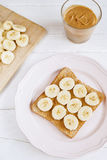 Toast with homemade peanut butter and banana on a white table. Top view. Selective focus Stock Photo