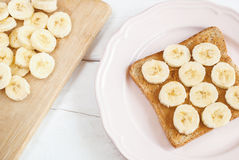 Toast with homemade peanut butter and banana on a white table. Top view. Selective focus Stock Photography