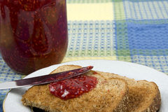 Toast and Jam. On a plate with jam jar in the background Royalty Free Stock Photo