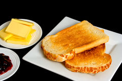 Toast and Jam. Fresh toast served with jam and butter isolated over black background Stock Image