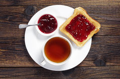 Toast with jam and tea. Toast with jam and cup of tea on dark wooden table. Top view royalty free stock photos