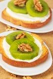 Toast with kiwi, cheese and walnuts Stock Photos