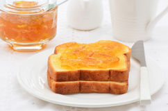 Toast with marmalade. Toasted white bread with orange marmalade, white dishes, horizontal composition Stock Images