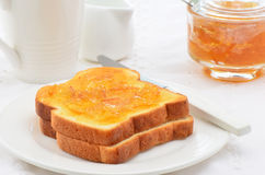 Toast with marmalade. Toasted white bread with orange marmalade, white dishes, horizontal composition Stock Photos