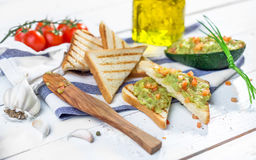 Toast with mashed avocado, olive oil and tomato Royalty Free Stock Images