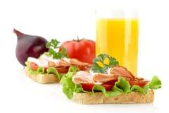 Toast mit Aufschnitt zum Frühstück brechen mit Orangensaft auf Weiß Lizenzfreie Stockbilder