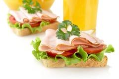 Toast mit Aufschnitt zum Frühstück mit Orangensaft auf Weiß Lizenzfreies Stockfoto