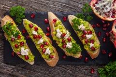 Toast mit Avocado und Granatapfel auf Holztisch Stockfoto