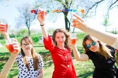 Toast mit Kinderchampagner auf Geburtstagsgartenfest - Plastikschalen lizenzfreies stockfoto