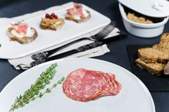 Toast mit Parma-, Salami- und Ganspastete auf einem weißen hackenden Brett stockbild