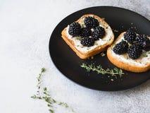 Toast mit Sahne Käse, Brombeeren, Thymian und Honig auf einem Schwarzblech Köstliches Frühstück mit vegetarischen Toast des neuen Lizenzfreies Stockbild