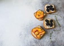 Toast mit Sahne Käse, Pfirsich oder Brombeeren, Thymian und Honig auf grauem Hintergrund Köstliches Frühstück mit Toast des neuen Lizenzfreie Stockfotos