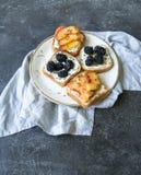 Toast mit Sahne Käse, Pfirsich oder Brombeeren, Thymian und Honig auf weißer Platte Köstliches Frühstück mit vegetarischen Toast  Stockbild
