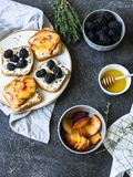 Toast mit Sahne Käse, Pfirsich oder Brombeeren, Thymian und Honig auf weißer Platte Köstliches Frühstück mit Toast von frischen B Stockbild