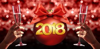 Toast New Year`s Eve, hands with glass of sparkle wine with chri. Stmas ball  on red blurred lights with 2018 text Royalty Free Stock Images