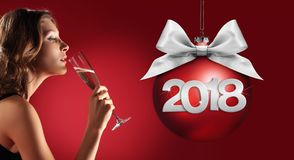 Toast New Year`s Eve, woman drinking sparkle wine on red backgro. Und with christmas ball and 2018 text royalty free stock image