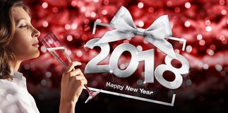 Toast New Year`s Eve, woman drinking sparkle wine on red blurred. Christmas lights with happy new year text Stock Image