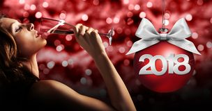 Toast New Year`s Eve, woman drinking sparkle wine on red blurred. Christmas lights with happy new year text royalty free stock photography