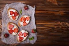 Toast oder bruschetta mit Erdbeeren auf Frischkäse auf hölzernem Hintergrund Stockfotos