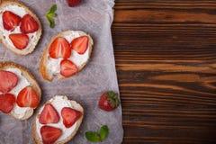 Toast oder bruschetta mit Erdbeeren auf Frischkäse auf hölzernem Hintergrund Lizenzfreie Stockbilder