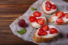Toast oder bruschetta mit Erdbeeren auf Frischkäse auf hölzernem Hintergrund Stockbild