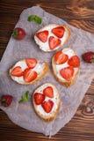 Toast oder bruschetta mit Erdbeeren auf Frischkäse auf hölzernem Hintergrund Lizenzfreie Stockfotografie
