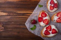 Toast oder bruschetta mit Erdbeeren auf Frischkäse auf hölzernem Hintergrund Stockbilder