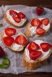 Toast oder bruschetta mit Erdbeeren auf Frischkäse auf hölzernem Hintergrund Stockfotografie