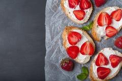 Toast oder bruschetta mit Erdbeeren auf Frischkäse auf schwarzem Hintergrund Stockbilder