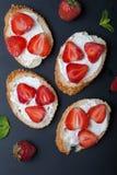 Toast oder bruschetta mit Erdbeeren auf Frischkäse auf schwarzem Hintergrund Stockbild