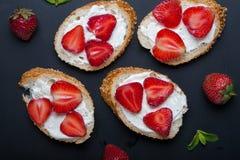 Toast oder bruschetta mit Erdbeeren auf Frischkäse auf schwarzem Hintergrund Stockfoto
