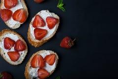 Toast oder bruschetta mit Erdbeeren auf Frischkäse auf schwarzem Hintergrund Lizenzfreies Stockbild