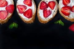 Toast oder bruschetta mit Erdbeeren auf Frischkäse auf schwarzem Hintergrund Lizenzfreies Stockfoto