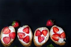 Toast oder bruschetta mit Erdbeeren auf Frischkäse auf schwarzem Hintergrund Lizenzfreie Stockfotografie