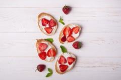 Toast oder bruschetta mit Erdbeeren auf Frischkäse auf weißem hölzernem Hintergrund Stockbild