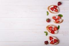 Toast oder bruschetta mit Erdbeeren auf Frischkäse auf weißem hölzernem Hintergrund Lizenzfreies Stockfoto