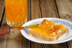 Toast with orange marmalade on wooden background Stock Photos