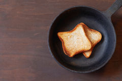 Toast in the pan. Frying pan and toast on dark wooden background Royalty Free Stock Images