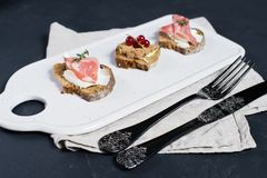 Toast with Parma, salami and goose pate on a white chopping Board stock photography