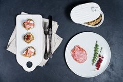 Toast with Parma, salami and goose pate on a white chopping Board royalty free stock image